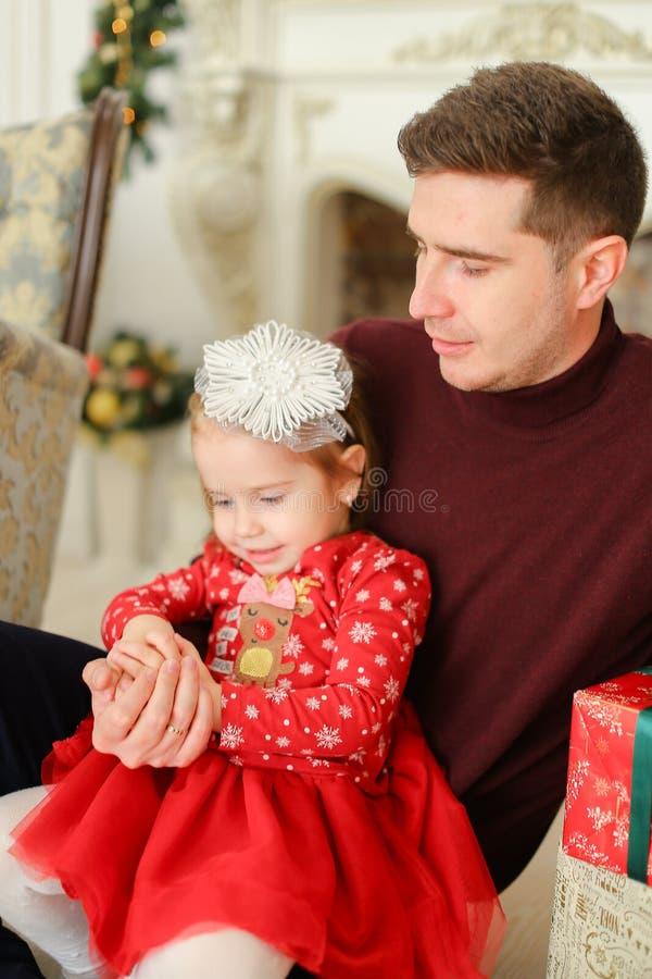穿红色礼服的小白肤金发的女儿坐与父亲近的装饰的墙壁 库存图片