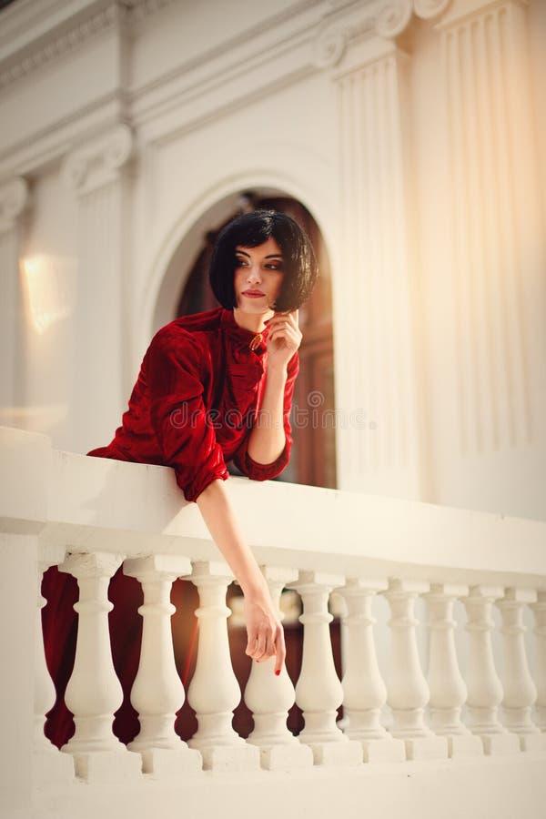 穿红色礼服的美丽的深色的妇女,摆在城堡 库存图片