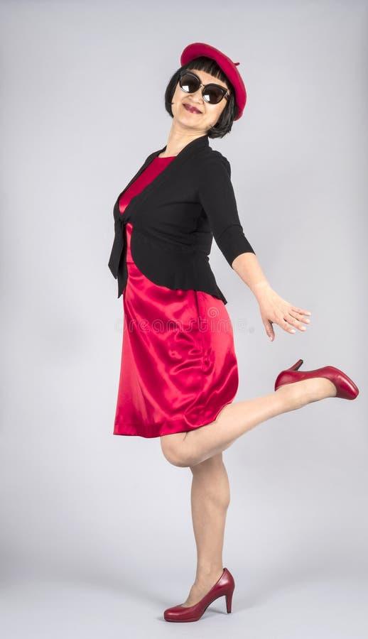 穿红色缎礼服和匹配红色贝雷帽帽子和红色皮革泵浦2的亚裔妇女 免版税库存照片