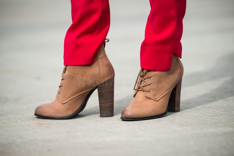穿红色裤子和棕色皮革高跟鞋鞋子的妇女在老镇 库存照片