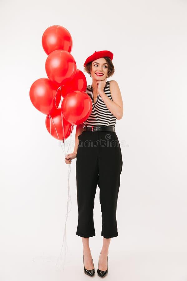 穿红色贝雷帽的一名微笑的妇女的全长画象 免版税库存图片