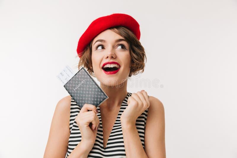穿红色贝雷帽的一名快乐的妇女的画象持护照 免版税库存图片