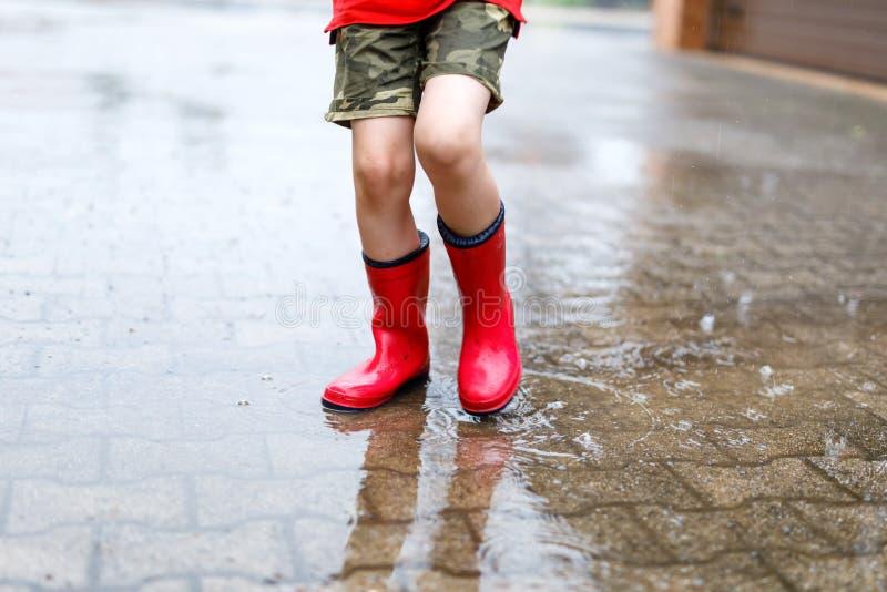 穿红色雨靴的孩子跳进水坑 免版税图库摄影
