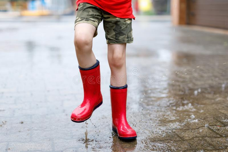 穿红色雨靴的孩子跳进水坑 图库摄影