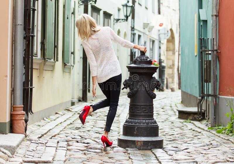穿红色高跟鞋鞋子的时髦的女人在老镇 库存照片