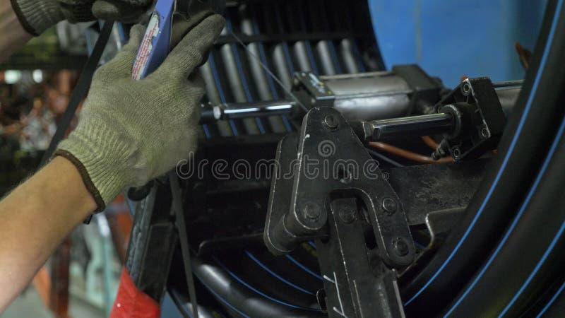 穿线卷管子的卷 塑料水管工厂制造  做塑料管的过程在机器 库存照片