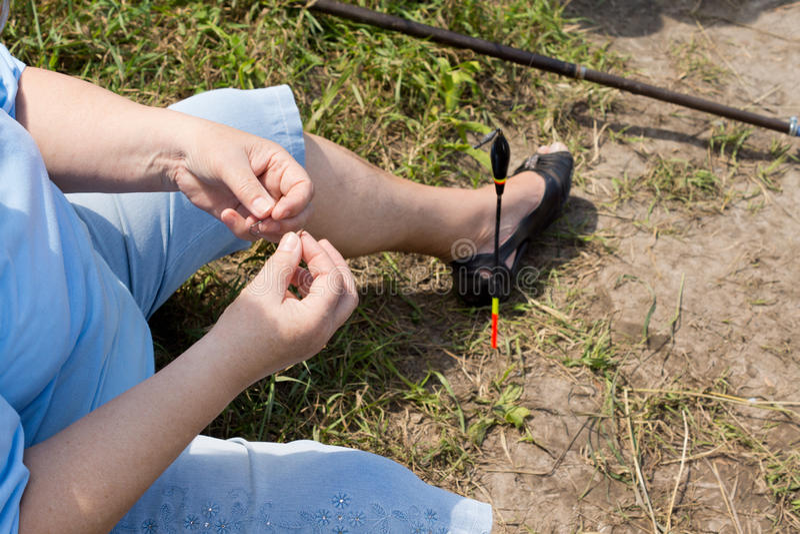穿线在她的勾子上的妇女诱饵,当钓鱼时 免版税库存照片