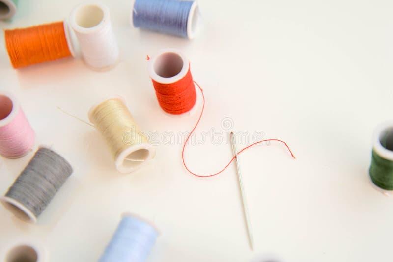 穿线的针、红色螺纹短管轴和多色的短管轴 免版税库存照片