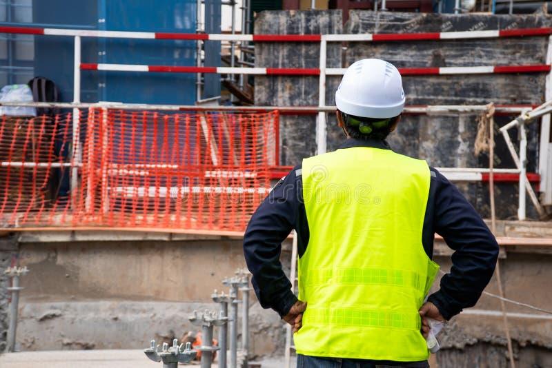 穿绿色安全衬衣的建筑监督员站立看前面检查在是的区域完成的工作 免版税库存照片