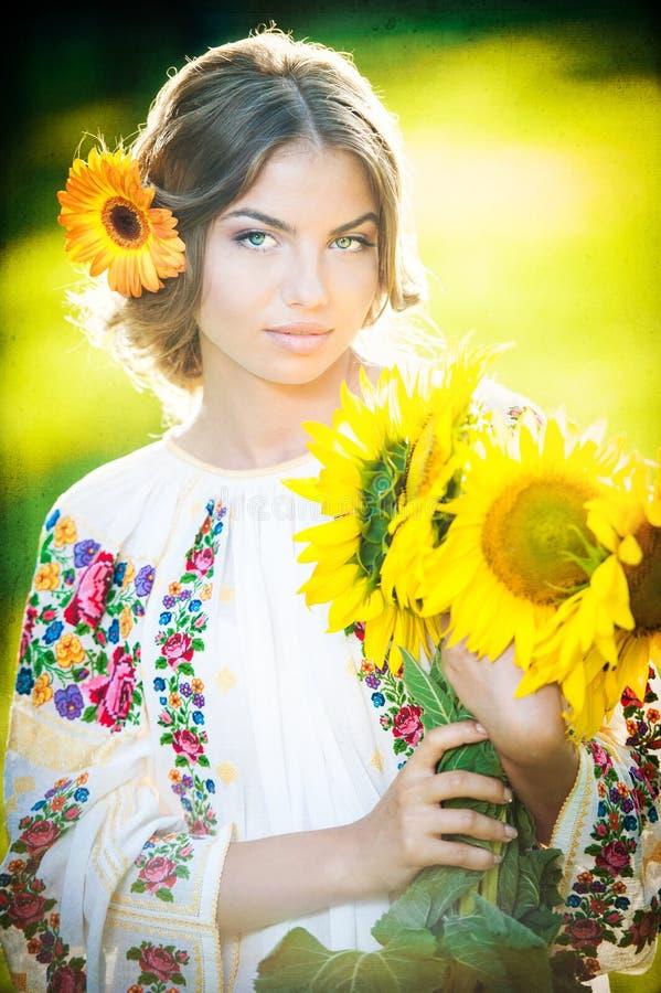 穿罗马尼亚传统女衬衫的女孩拿着向日葵室外射击。美丽的白肤金发的女孩画象用向日葵 免版税库存照片
