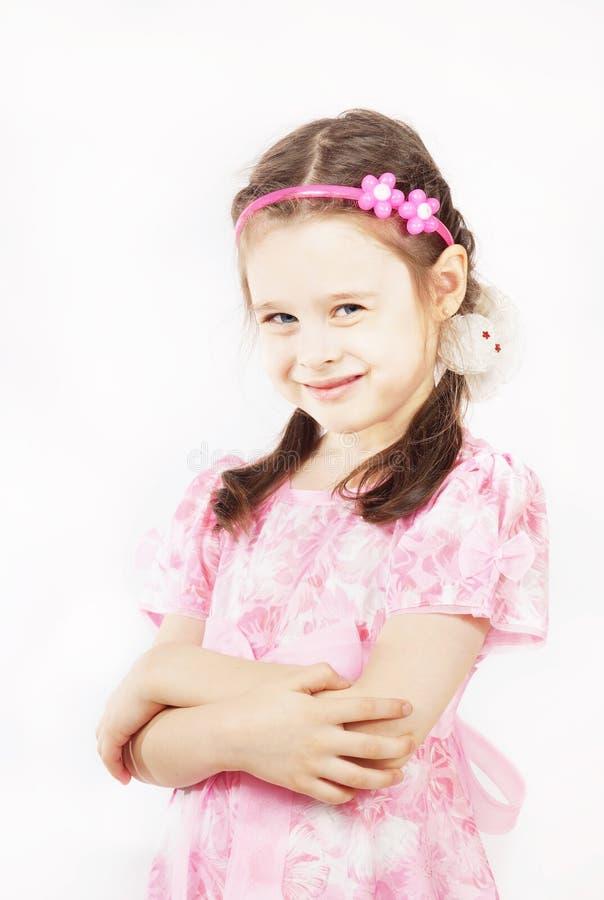 穿美丽的桃红色礼服的小俏丽的女孩微笑着 图库摄影