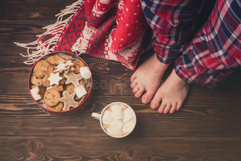穿舒适温暖的睡裤的女性脚刺激与姜饼曲奇饼杯与Marshmellow舒适圣诞节概念的热的Cococa 免版税库存图片