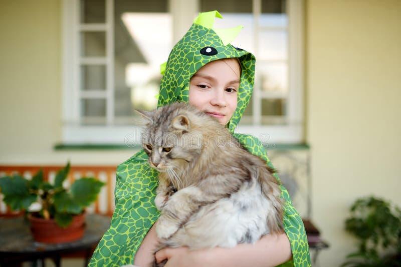 穿花梢服装的逗人喜爱的女孩拿着她的猫在晴朗的夏日 拿着het宠物全部赌注的可爱的孩子 免版税库存图片