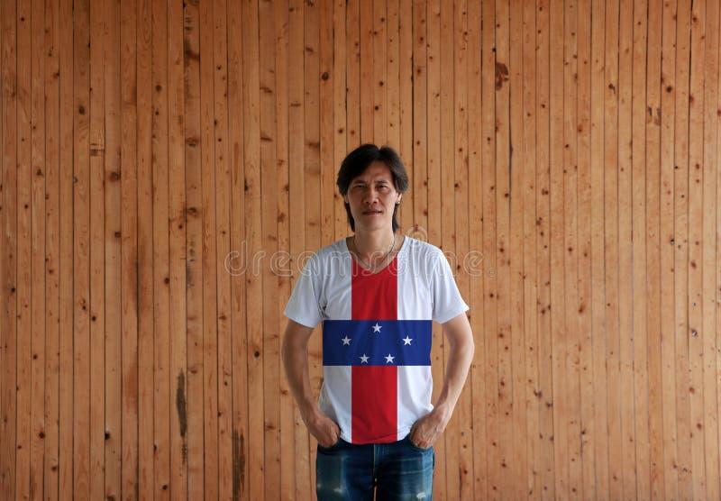 穿荷属安的列斯旗子颜色衬衣和站立用在裤兜的两只手的人在木墙壁背景 免版税库存图片