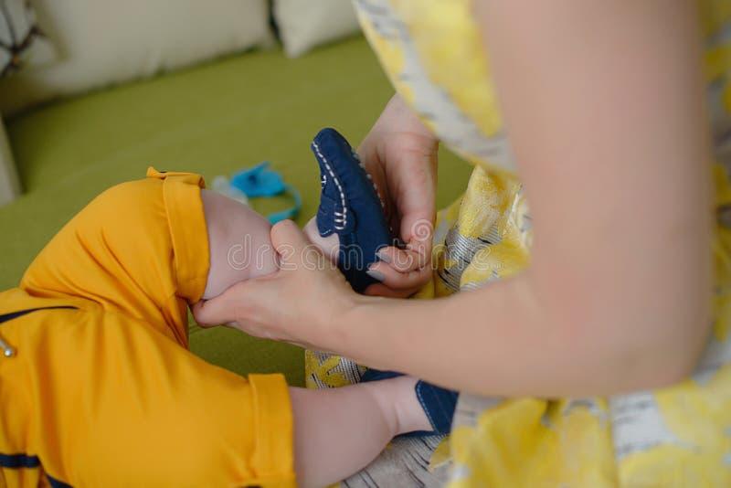 穿葡萄酒黄色礼服和帮助一点男婴的白种人年轻母亲准备好 库存图片