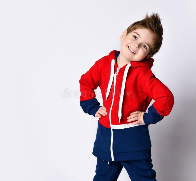 穿蓝红运动服的金发小男孩 他微笑着,把手放在臀部上,在白色工作室背景上摆出孤立的姿态 体育 库存图片