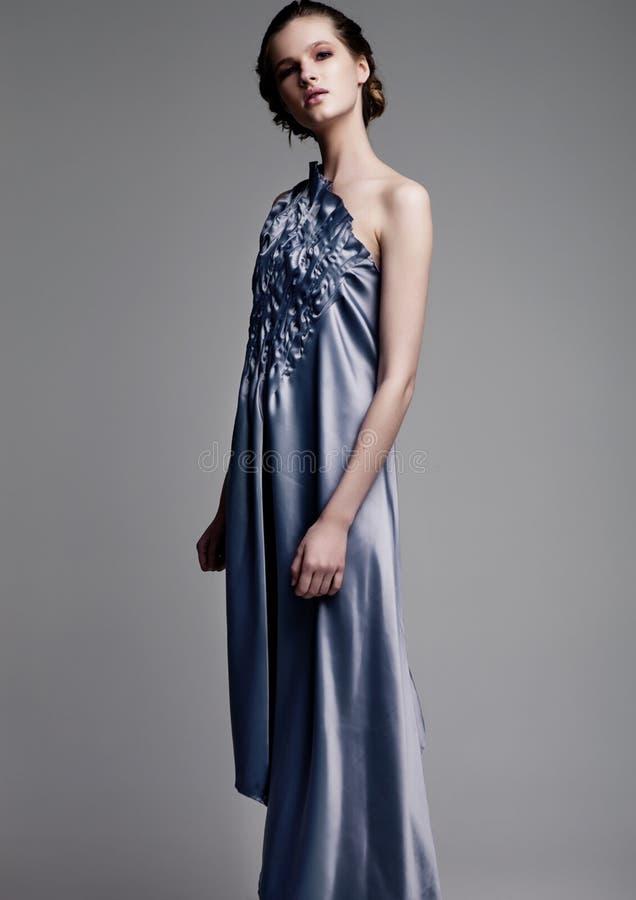 穿蓝色丝绸礼服的美好的时装模特儿 免版税图库摄影