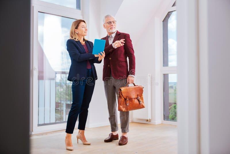 穿蓝色服装的时髦的美丽的房地产经纪商谈话与她的客户 库存图片
