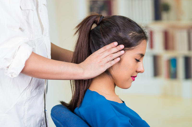 穿蓝色毛线衣的可爱的深色的办公室妇女坐由接受顶头按摩,应力消除概念的书桌 库存照片
