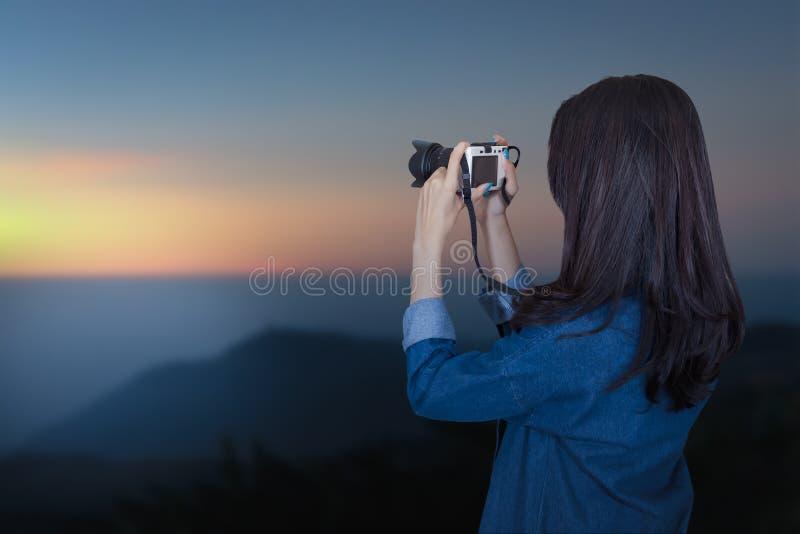 穿蓝色礼服的妇女旅客作为摄影师 图库摄影