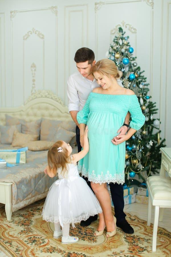 穿蓝色礼服的怀孕的女性站立与丈夫和小女儿在圣诞树附近 免版税图库摄影