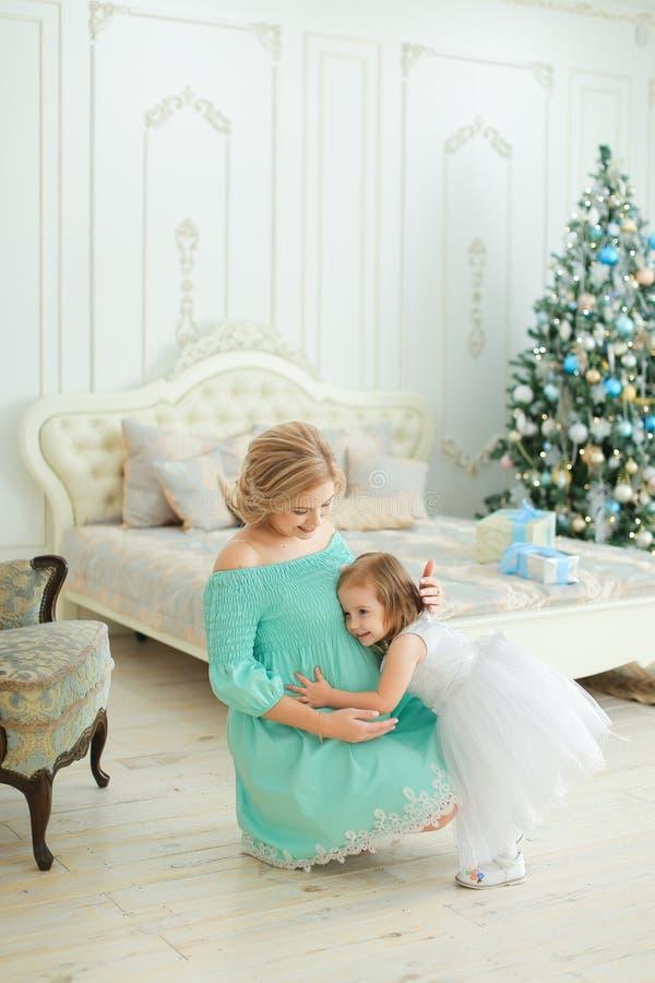 穿蓝色礼服的怀孕的欧洲妇女拥抱腹部和坐与小女儿在圣诞树附近在卧室 库存图片