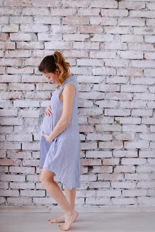 穿蓝色礼服的怀孕的cauca欧洲人西安妇女站立在砖墙背景中和握腹部 免版税图库摄影