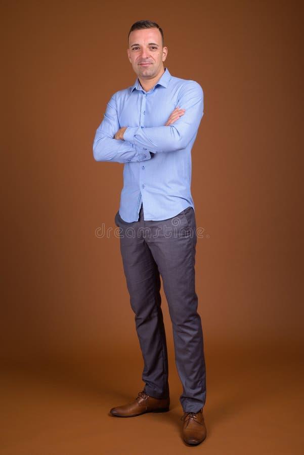 穿蓝色衬衣的商人全长射击 免版税库存照片
