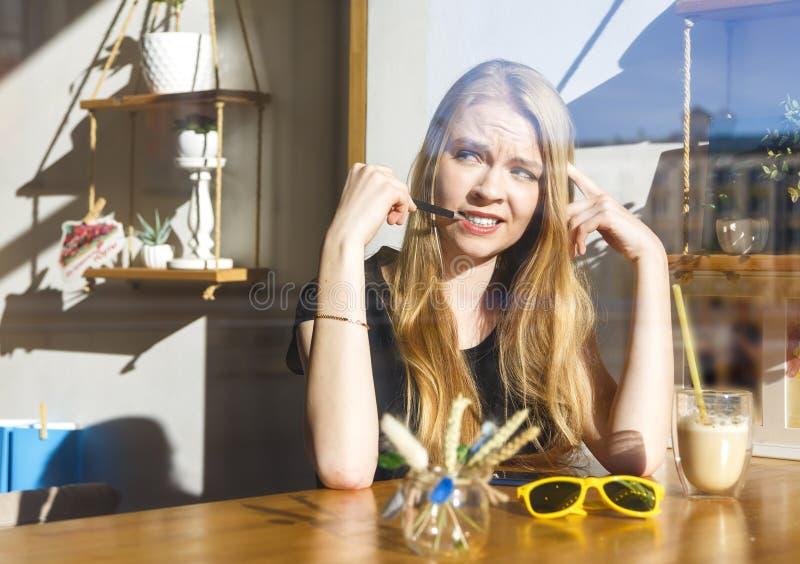 穿蓝色衬衣的少女在与大杯的一个咖啡馆坐拿铁 在玻璃vitrine后 好的温暖的射击年轻 图库摄影