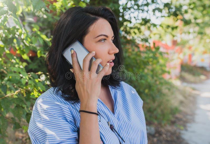 穿蓝色衬衣的快乐的年轻白种人妇女谈话在关于新的项目的手机 人们、生活方式和事务 图库摄影