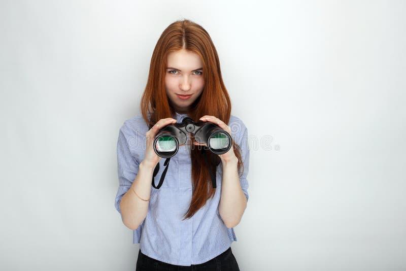 穿蓝色镶边衬衣的年轻逗人喜爱的红头发人妇女画象微笑充满幸福和喜悦,当再时摆在与双筒望远镜 免版税库存图片