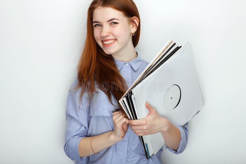 穿蓝色镶边衬衣的年轻逗人喜爱的红头发人妇女画象微笑充满幸福和喜悦,当摆在与唱片aga时 库存图片