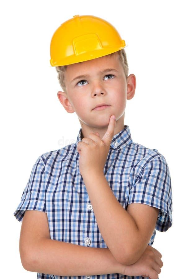 穿蓝色T恤杉和黄色安全帽的一个体贴的男孩的半身情感画象,隔绝在白色背景 图库摄影