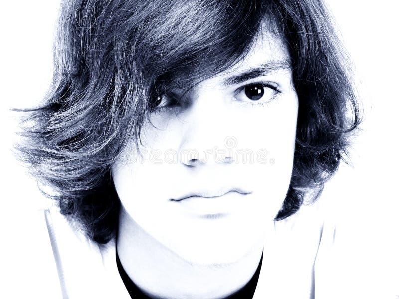 穿蓝衣的男孩关闭青少年的口气 免版税库存图片