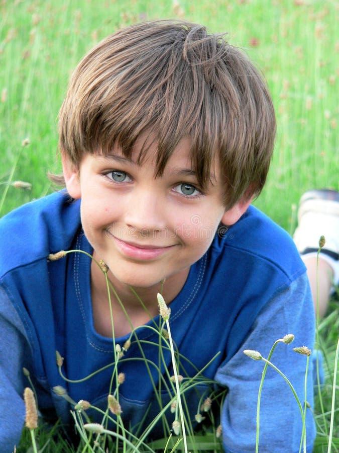 穿蓝衣的男孩域绿色一点 库存照片
