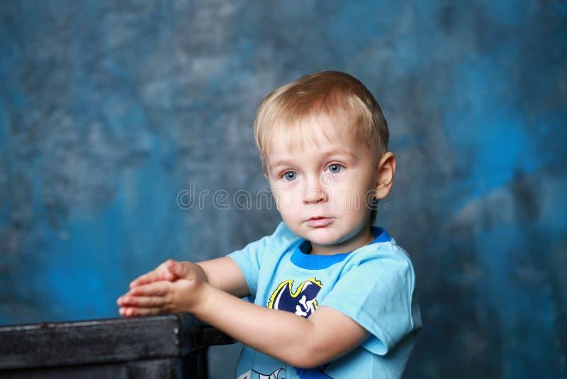穿蓝衣的男孩注视一点 免版税库存图片