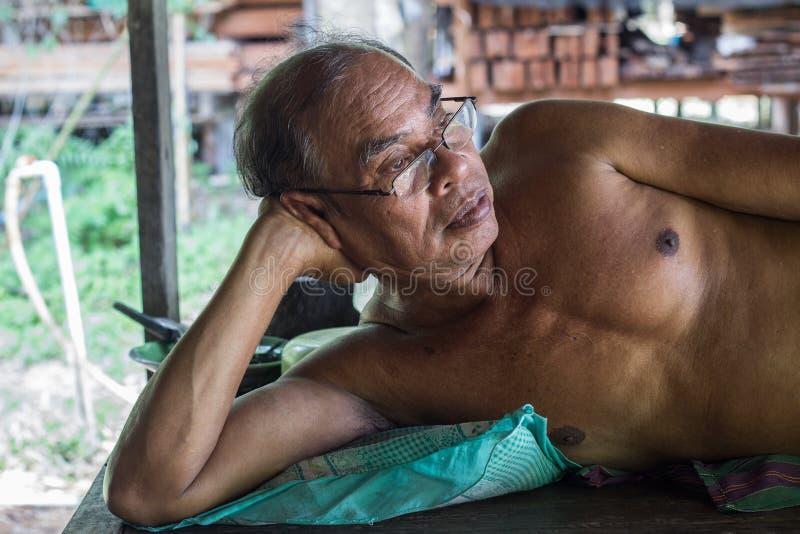 穿衬衣的泰国年迈的人说谎在床上 免版税库存图片