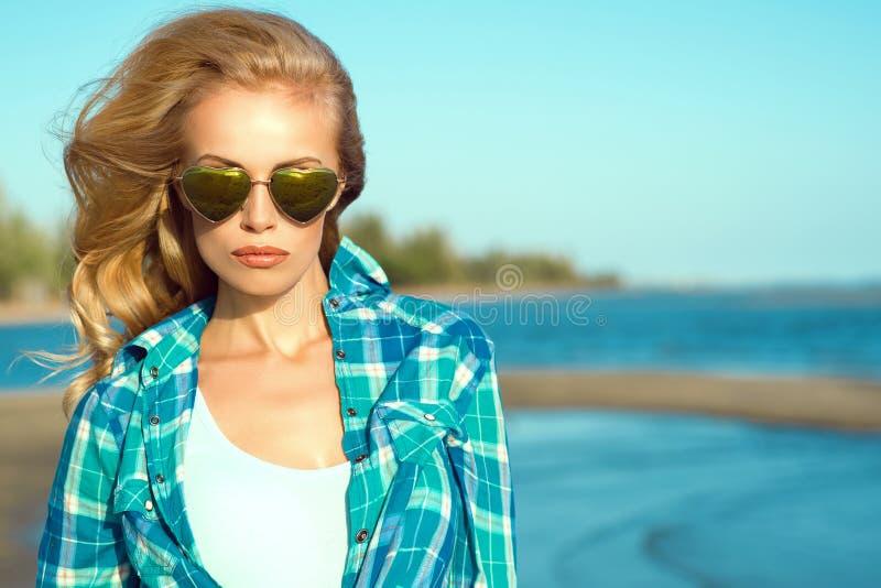 穿被反映的心形的太阳镜和被检查的蓝色衬衣的年轻华美的性感的被晒黑的白肤金发的模型画象在海 免版税库存照片