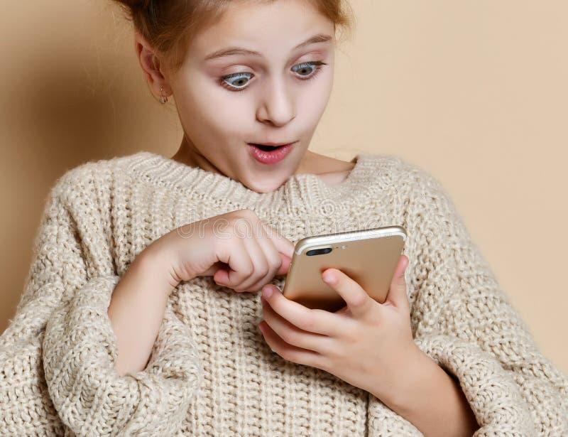 穿被编织的帽子、围巾和毛线衣的愉快的小女孩冬天画象  白色木背景的孩子 秀丽蓝色聪慧的概念表面方式构成妇女 免版税库存图片