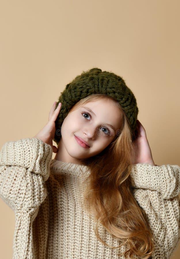 穿被编织的帽子和毛线衣的愉快的女孩冬天画象 免版税库存照片