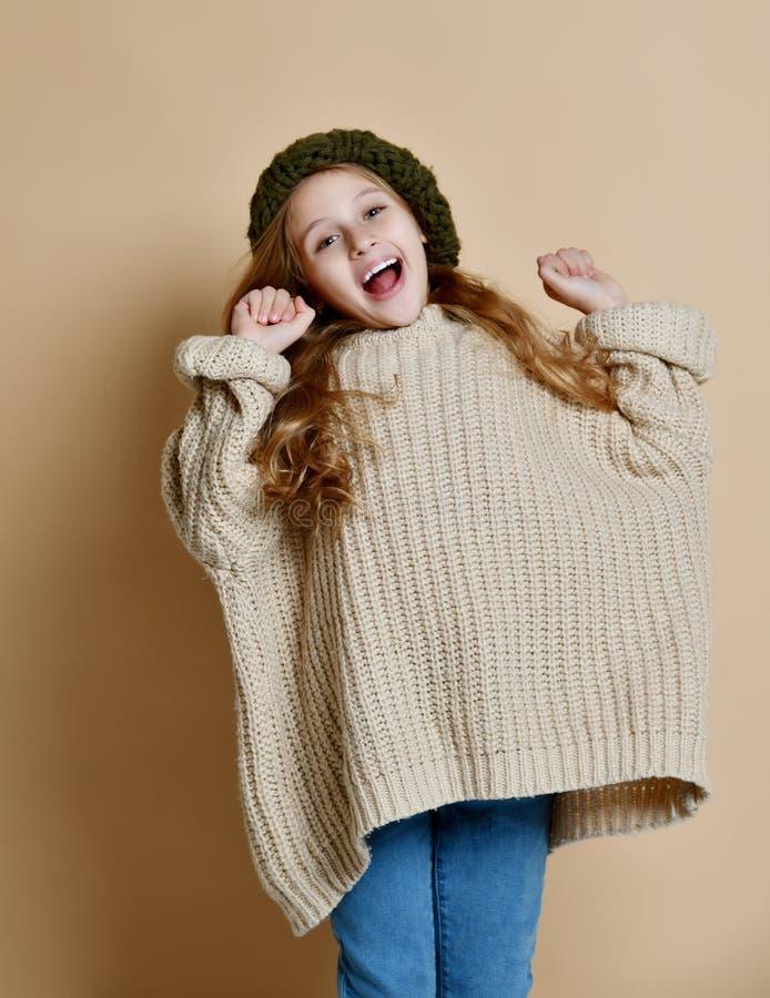 穿被编织的帽子和毛线衣的愉快的女孩冬天画象 库存照片