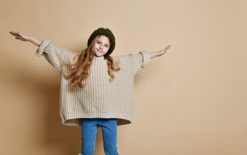 穿被编织的帽子和毛线衣的愉快的女孩冬天画象 免版税库存图片