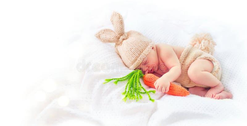 穿被编织的兔宝宝服装的逗人喜爱的新出生的男婴 免版税图库摄影