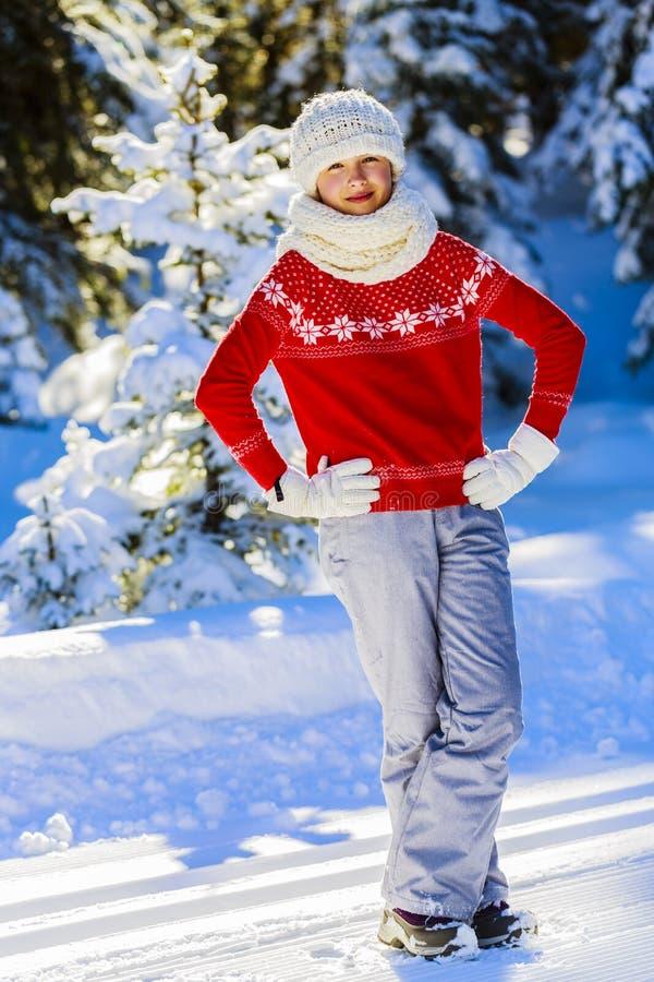 穿被编织的穿戴围巾的愉快的冬天女孩 免版税库存照片