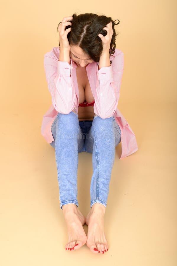 穿被解扣的衬衣的沮丧的恼怒的沮丧的少妇显示她分裂 库存照片