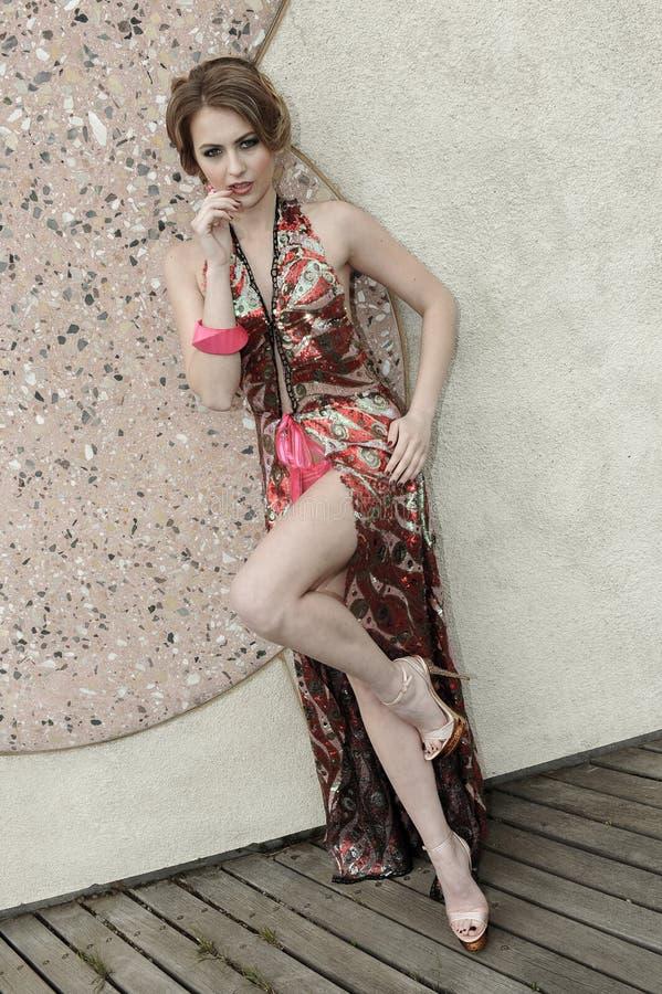穿豪华旅游胜地礼服的美丽的少妇 免版税库存照片