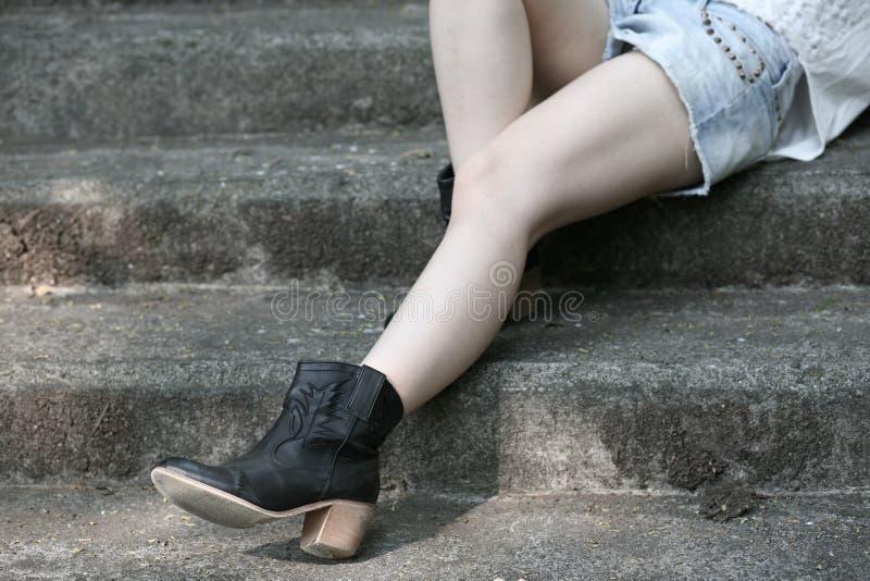 穿起动的腿躺下在水泥步 免版税图库摄影