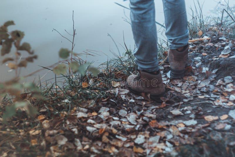 穿轻的牛仔裤和起动的一个人支持河 种类腿 ?? ?? r 库存照片