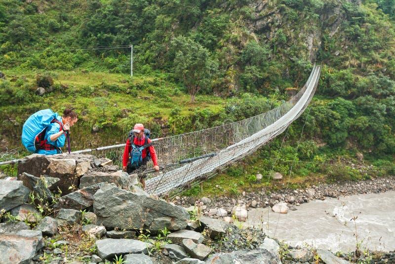 穿过吊桥的游人河 免版税库存图片