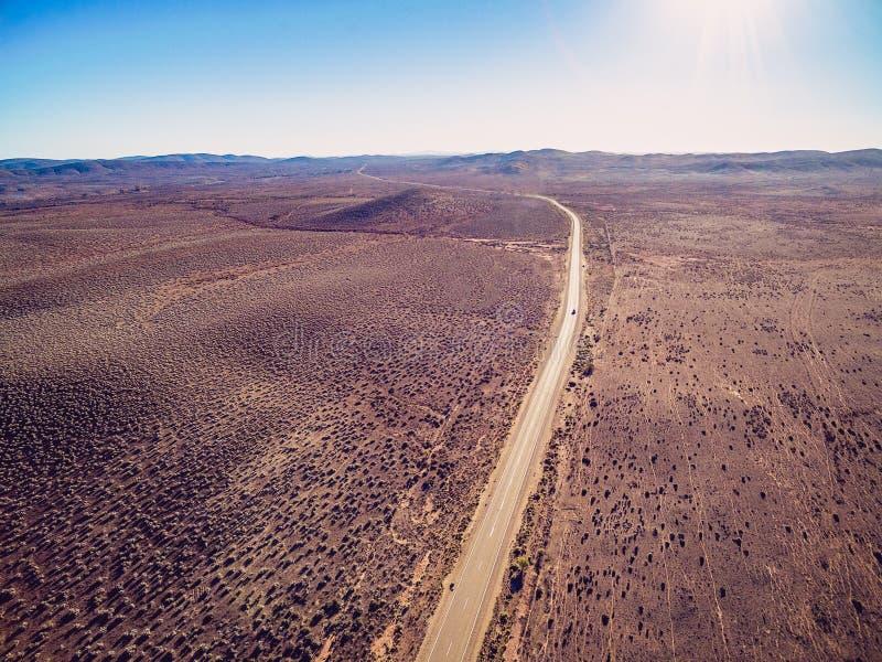 穿过有缺乏植被的干陆的农村路 免版税库存图片